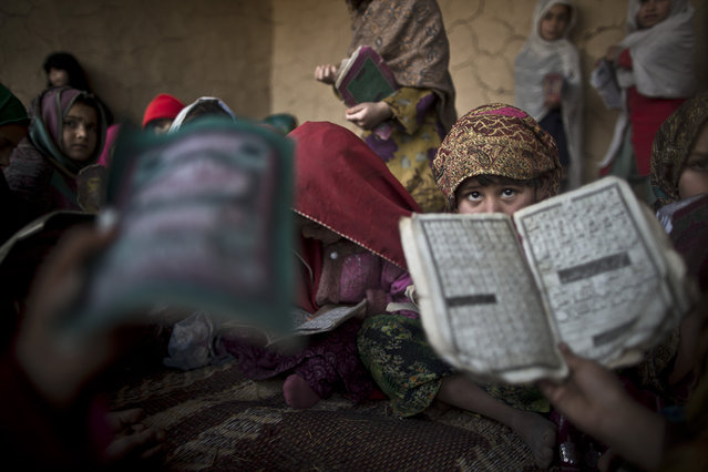 In this Tuesday, January 28, 2014, photo, Pakistani children, whose families were displaced from Pakistan's tribal areas due to fighting between the Taliban and the army, hold booklets of Urdu alphabets and verses of the Quran, and repeat after their teacher during their daily Madrassa, or Islamic school, at a mosque on the outskirts of Islamabad, Pakistan. (Photo by Muhammed Muheisen/AP Photo)
