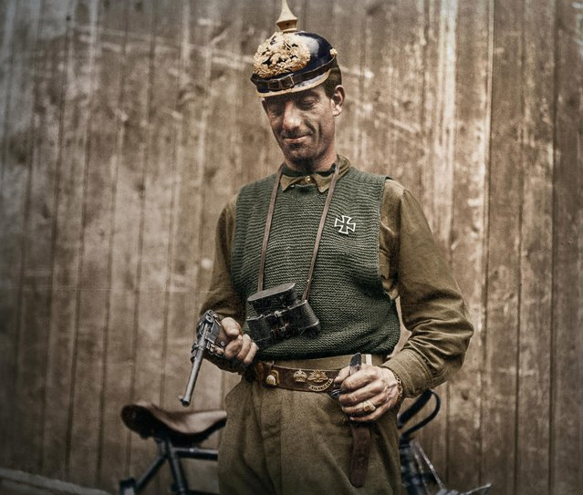 One image shows an unidentified American soldier posing with a pistol, helmet, and Iron Cross medal taken from a German soldier, 1918. (Photo by Mario Unger/Mediadrumworld)
