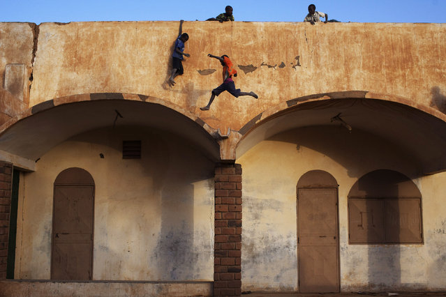Boys play on the roof of the entrance to a football stadium in Gao February 20, 2013. (Photo by Joe Penney/Reuters)