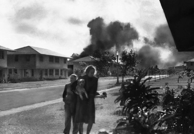 "Officers' wives, investigating explosions and seeing smoke in the distance, heard neighbor Mary Naiden, then an Army hostess who took this picture, exclaim ""There are red circles on those planes overhead. They are Japanese!"" Realizing war had come, the two women, stunned, started toward quarters. (Mary Naiden/Associated Press)"