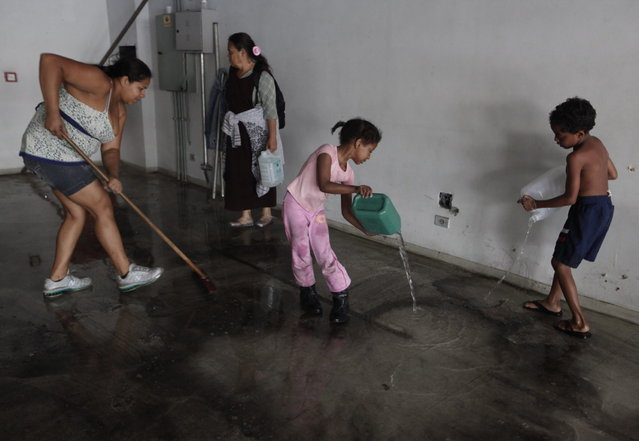 Members of Brazil's Movimento dos Sem-Teto (Roofless Movement) clean a vacant apartment they chose, in one of the 11 empty buildings that the movement took over in one night, in the centre of Sao Paulo, October 29, 2012. According to City Hall, there are some 400,000 people in need of stable housing, including the 4,000 families of the Roofless Movement who are squatting in abandoned or vacant buildings that range from apartment blocks to hotels, in Sao Paulo, the largest city in South America. (Photo by Nacho Doce/Reuters)