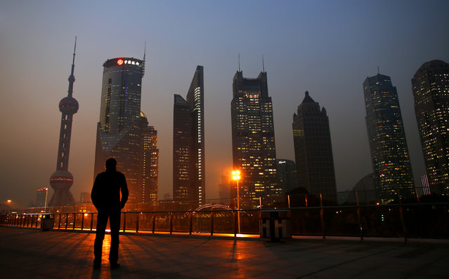 A man looks at the Pudong financial district of Shanghai on November 20, 2013. (Photo by Carlos Barria/Reuters)