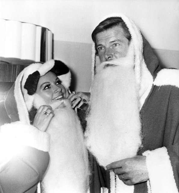 """Actors Luisa Mattioli and her husband Roger Moore don """"Father Christmas"""" costumes at the Variety Club of Great Britain's Christmas luncheon at the Savoy Hotel in London, December 9, 1969.  They are collecting gifts for sick and deprived children. (Photo by Bob Dear/AP Photo)"""