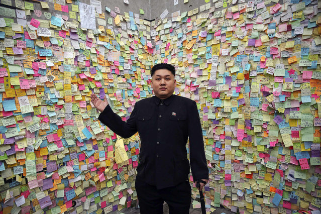 Howard, a 35-year-old Australian Chinese musician and lookalike of North Korean leader Kim Jong Un, gestures in front of a wall with messages of support to pro-democracy protesters in part of Hong Kong's financial central district they are occupying October 31, 2014. (Photo by Damir Sagolj/Reuters)