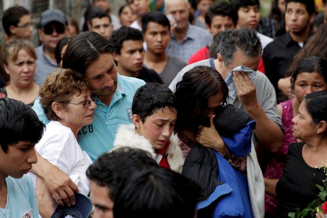 Relatives and friends of a mudslide victim mourn during his funeral service at a cemetery, in Santa Catarina Pinula, on the outskirts of Guatemala City, October 4, 2015. Despair in the search for hundreds of people buried in a landslide that swallowed part of a Guatemalan town is so deep that some relatives feel lucky simply to have found the bodies of their loved ones. (Photo by Josue Decavele/Reuters)