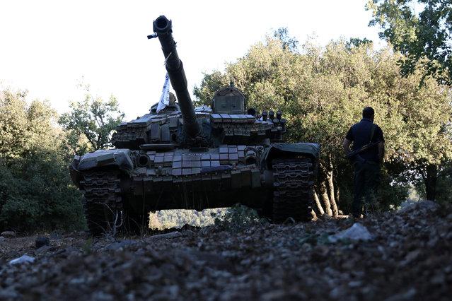 A rebel fighter walks next to a tank in Jubata al-Khashab, in Quneitra countryside, Syria September 11, 2016. (Photo by Alaa Al-Faqir/Reuters)