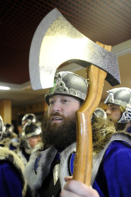 A participant dressed as a Viking holds his axe aloft as he prepares to participate in the annual Up Helly Aa festival in Lerwick, Shetland Islands on January 29, 2013. Up Helly Aa celebrates the influence of the Scandinavian Vikings in the Shetland Islands and culminates with up to 1,000 'guizers' (men in costume) throwing flaming torches into their Viking longboat and setting it alight later in the evening. AFP PHOTO / ANDY BUCHANAN        (Photo credit should read Andy Buchanan/AFP/Getty Images)