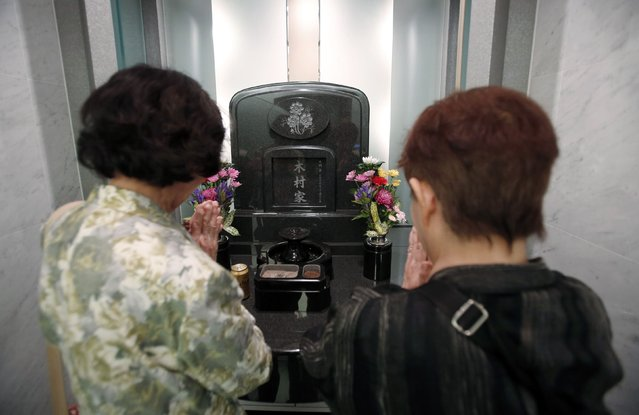 Yukiko Kimura (R) prays for her late husband Mitsugi with Mitsugi's sister Kiyoko Matsuura in front of a modern tomb that robotically retrieves the correct tombstone or urn based on which identity card is provided, at Ryogoku Ryoen, a multi-storey vault-style graveyard, in downtown Tokyo October 27, 2014. (Photo by Toru Hanai/Reuters)