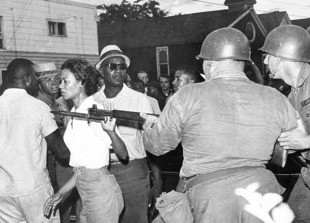 Mrs. Gloria Richardson, head of the Cambridge Nonviolent Action Committee, pushes a National Guardsman's bayonet aside as she moves among a crowd of African Americans to convince them to disperse, in Cambridge, Maryland, on July 21, 1963. (Photo by AP Photo)