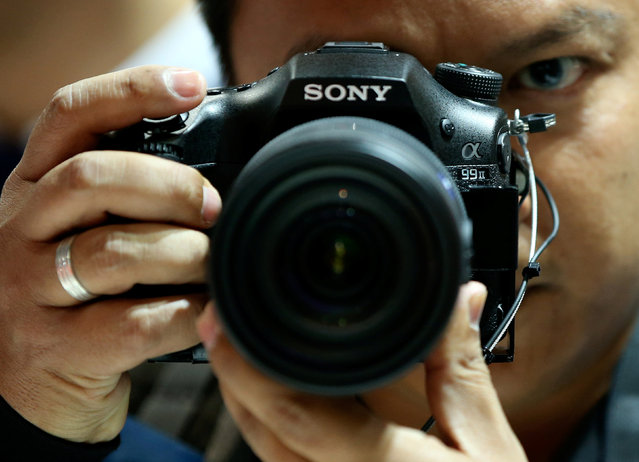 A visitor checks out the new Sony Alpha 99 Mark II DSLR camera at the Sony booth on the Photokina, the world's largest fair for imaging in Cologne, Germany, September 20, 2016. (Photo by Fabrizio Bensch/Reuters)