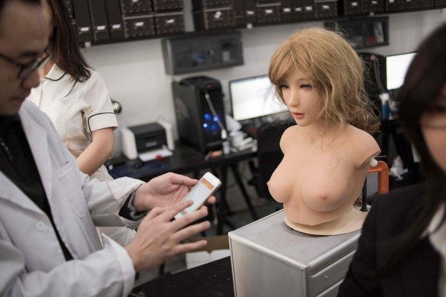 This photo taken on February 1, 2018 shows an engineer displaying the facial expressions a robot can make, in a lab of a doll factory of EXDOLL, a firm based in the northeastern Chinese port city of Dalian. (Photo by Fred Dufour/AFP Photo)