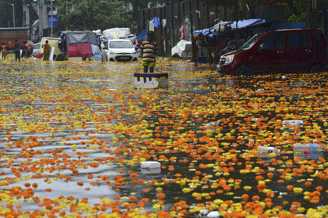A vendor stands in a flooded flower market following heavy monsoon rains in Mumbai on September 23, 2020. (Photo by Sujit Jaiswal/AFP Photo)