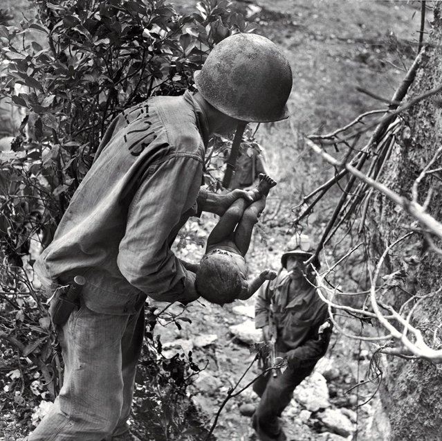 In a photo that somehow comprises both tenderness and horror, an American Marine cradles a near-dead infant pulled from under a rock while troops cleared Japanese fighters and civilians from caves on Saipan in the summer of 1944. The child was the only person found alive among hundreds of corpses in one cave. (Photo by W. Eugene Smith/Time & Life Pictures)