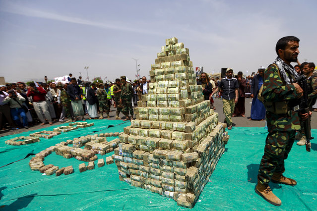 """A fighter loyal to Yemen's Huthi rebels stands guard next to a stack of bills in the capital Sanaa on September 24, 2020, during a ceremony by the Huthis to collect cash, food and other donations for their fighters. Huthi rebels marked 2,000 days of """"resistance"""" against the Saudi-led coalition in war-torn Yemen on with a display of stacks of cash, food and other donations presented to their fighters. (Photo by Mohammed Huwais/AFP Photo)"""