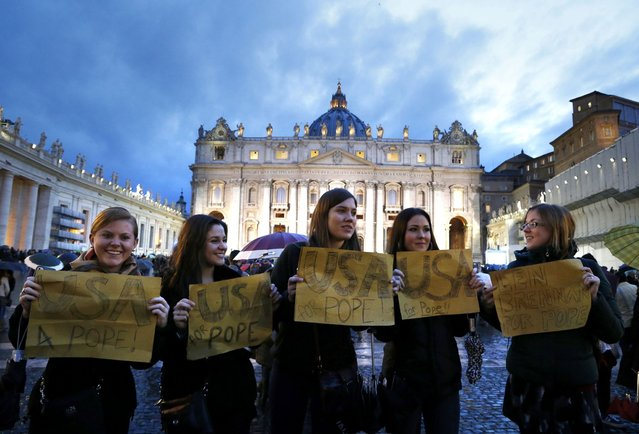 Women hold placards in support of the election of a U.S. cardinal to be named as pope, outside Saint Peter's Basilica and the Sistine Chapel at the Vatican March 12, 2013. Roman Catholic Cardinals began their conclave inside the Vatican's Sistine Chapel today to elect a new pope. (Photo by Stefano Rellandini/Reuters)