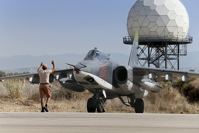 A Russian ground staff member signals to the pilot of a Sukhoi Su-25 fighter jet at the Hmeymim air base near Latakia, Syria, in this handout photograph released by Russia's Defence Ministry October 22, 2015. (Photo by Reuters/Ministry of Defence of the Russian Federation)