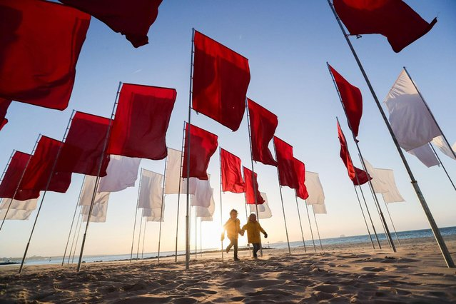 """An artwork by Luke Jerram entitled """"In Memoriam"""" has ben set up on Sandbanks beach in Poole, UK as part of the Bournemouth Arts by the Sea Festival on September 27, 2020. The Sea of flags made up of 100 bed sheets set up in the shape of a red cross on a white background offers the public a place to visit to remember those who have died during the COVID-19 pandemic and to pay tribute to NHS workers and volunteers caring for all those affected by the crisis. (Photo by Richard Crease/Alamy Live News)"""