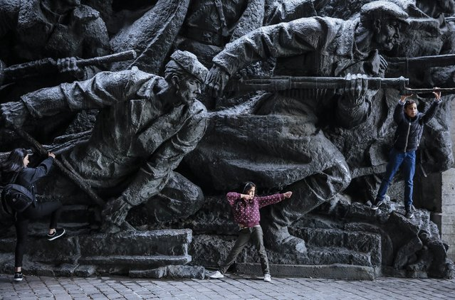 Children play next to the bronze monument at the World War II museum complex in Kiev, Ukraine, 28 October 2015. Ukrainians mark 71th anniversary of the liberation of Ukraine from the Nazi occupation during WWII. (Photo by Roman Pilipey/EPA)
