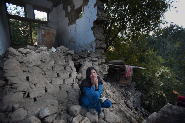 A Pakistani woman, who lost her two grandsons in Monday's earthquake, mourns as she sits on the rubble of her destroyed home, in Jinjara village in Chitral, a district of Northern Pakistan, Wednesday, October 28, 2015. Afghanistan and Pakistan were scrambling Wednesday to rush aid to survivors of this week's magnitude-7.5 earthquake as the region's overall death toll from the temblor rose more than 380. (Photo by Anjum Naveed/AP Photo)