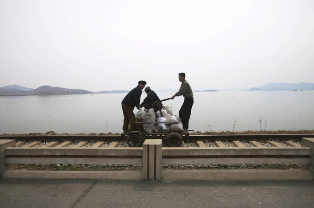 In this April 21, 2011 photo, men operate a manual rail car on tracks running along the West Sea barrage near Nampho, North Korea. (Photo by David Guttenfelder/AP Photo)