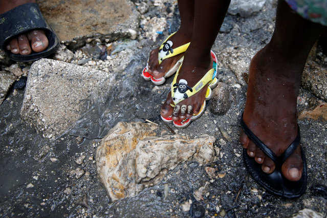 People walk on a flooded street after Hurricane Matthew passes Cite-Soleil in Port-au-Prince, Haiti, October 5, 2016. (Photo by Carlos Garcia Rawlins/Reuters)