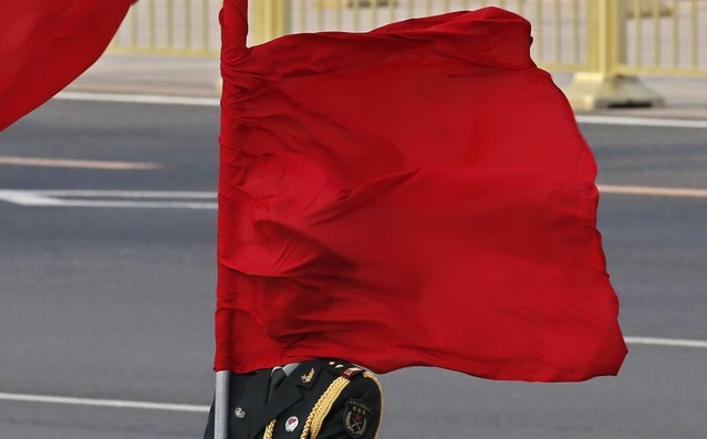 The wind blows a red flag onto the face of an honour guard before a welcome ceremony for Australia's Prime Minister Julia Gillard outside the Great Hall of the People in Beijing April 9, 2013. (Photo by Kim Kyung-Hoon/Reuters)