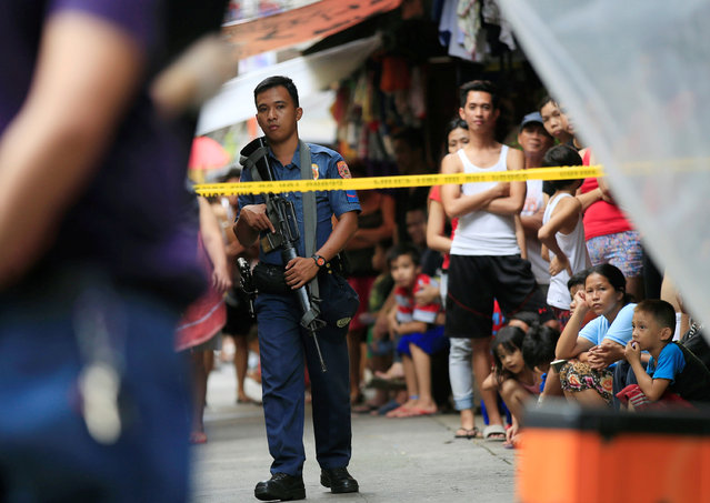 A member of the Philippine National Police (PNP) stands guard while residents look on near the scene where two suspected drug pushers were killed during a police operation, in metro Manila, Philippines October 8, 2016. (Photo by Romeo Ranoco/Reuters)