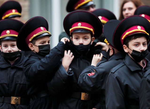 Young military adjust each others uniforms for a ceremony of receiving their shoulder marks in Kyiv, Ukraine on November 6, 2020. (Photo by Gleb Garanich/Reuters)