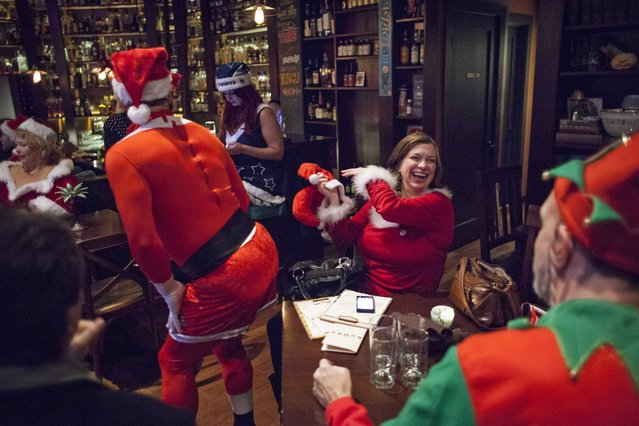 Marlene Webb (R) laughs as a fellow Santarchy participant dances for her table at Rumba in Seattle, Washington December 13, 2014. (Photo by David Ryder/Reuters)