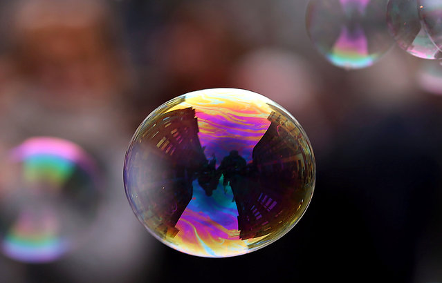 Buildings reflected in a soap bubble during the performance of a street artist in Cologne, Germany, October 16, 2015. (Photo by Oliver Berg/EPA)