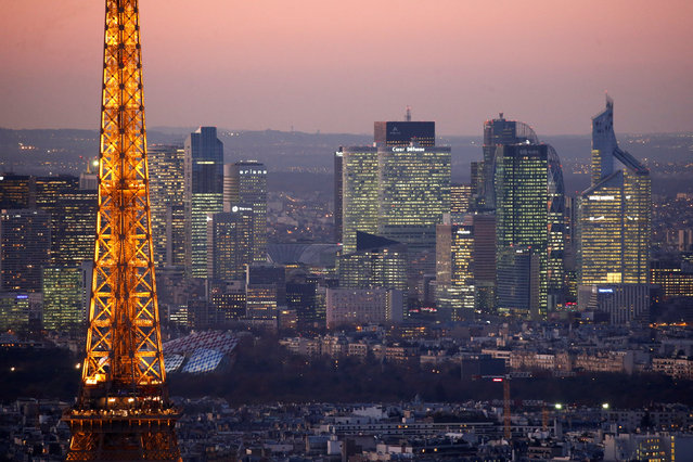 A general view shows the illuminated Eiffel Tower and the skyline of La Defense business district (Rear) at night in Paris, France, November 28, 2016. (Photo by Charles Platiau/Reuters)