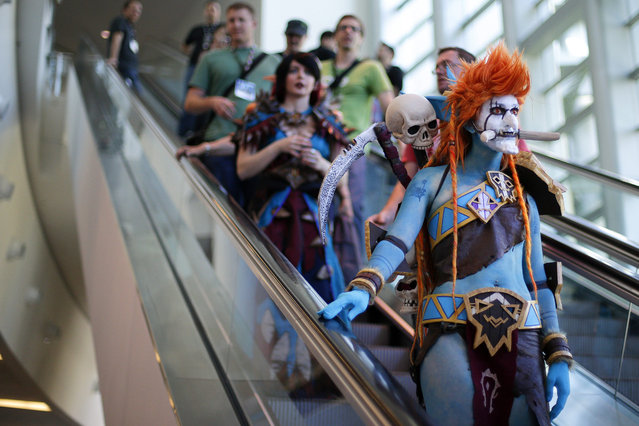 "A woman dressed as Voljin from the video game World of Warcraft rides an escalator at the BlizzCon, Friday, November 6, 2015, in Anaheim, Calif. ""World of Warcraft"" maker Blizzard is hosting its ninth annual fan-centric convention opening Friday. (Photo by Jae C. Hong/AP Photo)"