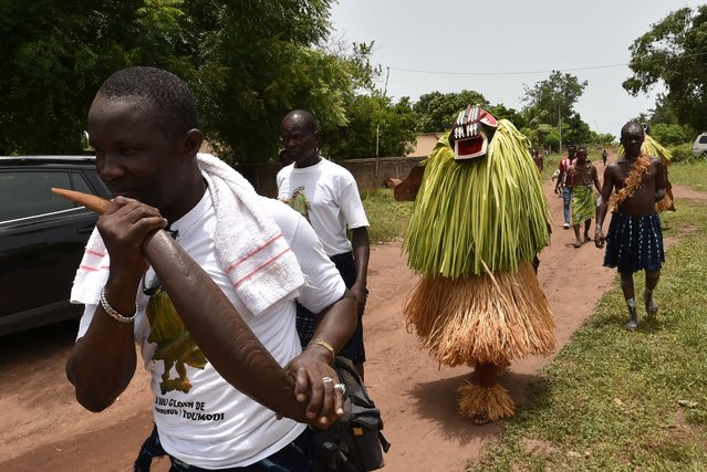 """A person from the Baoule community wearing a Goly mask and guides arrive to perform at the youth residence in Assounvoue village, part of Toumodi, central Ivory Coast, on March 31, 2018 on the eve of """"Paquinou"""", easter celebration traditionally marked by """"palaver"""", reconciliation, feast, music and dance. (Photo by Sia Kambou/AFP Photo)"""