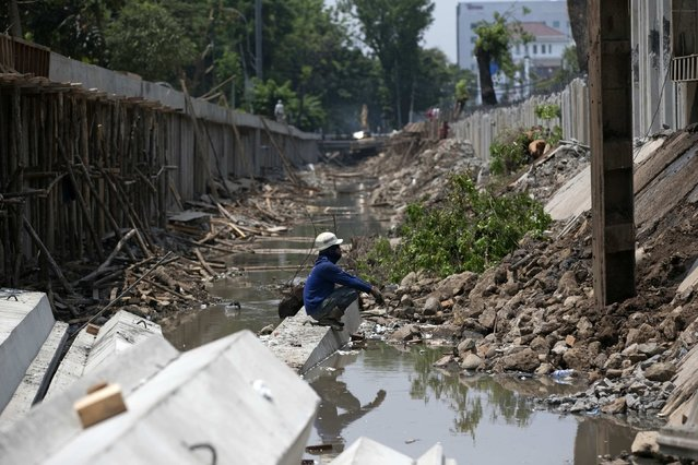 A worker sits on a concrete section of a reinforcement wall to be used to strengthen and widen a river bank running through central Jakarta in this October 31, 2014 file photo. (Photo by Darren Whiteside/Reuters)