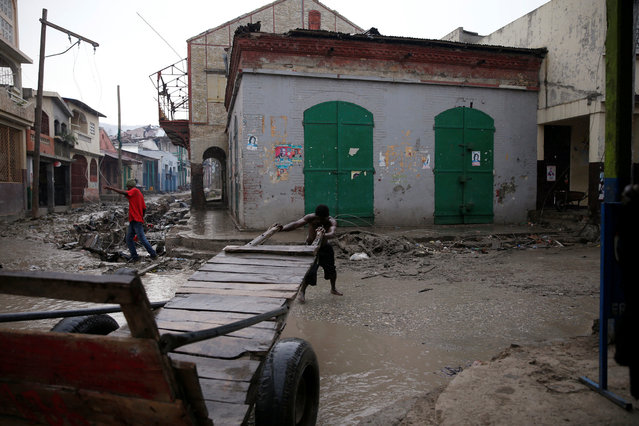 A man pushes a wheelbarrow in a flooded street after Hurricane Matthew hit Jeremie, Haiti, October 14, 2016. (Photo by Carlos Garcia Rawlins/Reuters)