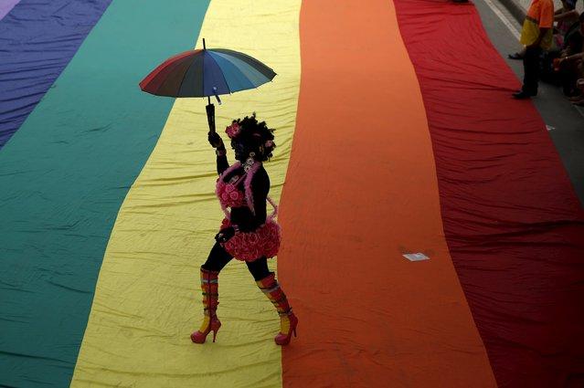 A reveller takes part in the LGBT Pride Parade in Copacabana beach in Rio de Janeiro, Brazil, November 15, 2015. (Photo by Pilar Olivares/Reuters)