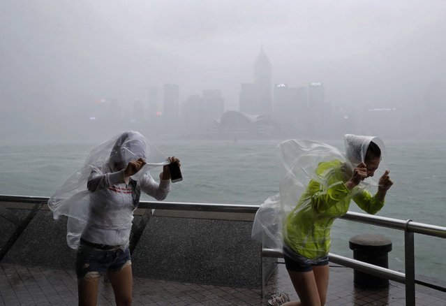 People brave the wind on the waterfront of Victoria Habour as Typhoon Haima approaches Hong Kong, Friday, October 21, 2016. (Photo by Vincent Yu/AP Photo)