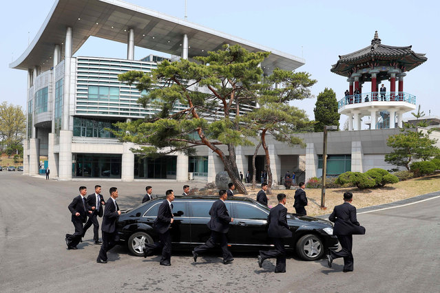 North Korean security persons run by a car carrying North Korean leader Kim Jong Un return to the North side for a lunch break after a morning session of a summit meeting with South Korean President Moon Jae-in at the border village of Panmunjom in Demilitarized Zone Friday, April 27, 2018. (Photo by Korea Summit Press Pool via AP Photo)