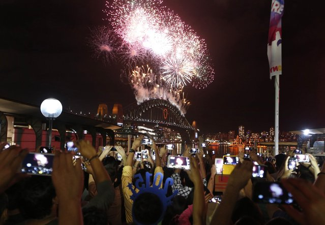 Crowds watch as fireworks light up the Sydney Harbour Bridge during the annual fireworks display January 1, 2015. (Photo by David Gray/Reuters)