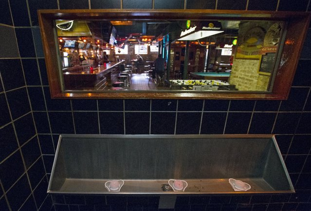 A one-way mirror is seen above the urinal at Streeter's Tavern in Chicago, Illinois, United States, September 30, 2015. Customers using the the bathroom can see into the main area of the bar, but cannot be seen by the people at the bar. (Photo by Jim Young/Reuters)