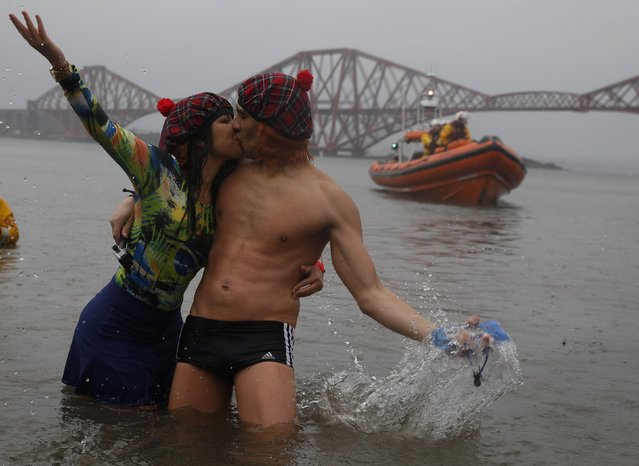 Swimmers in fancy dress kiss as they participate in the New Year's Day Loony Dook swim at South Queensferry, Scotland, January 1, 2015. (Photo by Russell Cheyne/Reuters)