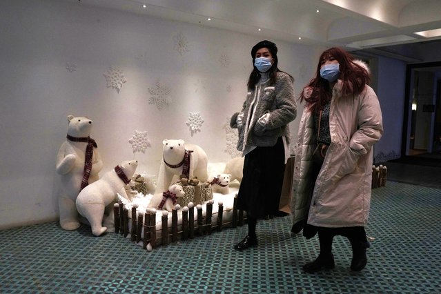 Residents wearing masks to protect from the coronavirus walks past decorations depicting polar bears in Beijing Tuesday, December 29, 2020. As temperatures plunge to near record lows, the Chinese capital is strengthening measures as new cases of coronavirus are reported. (Photo by Ng Han Guan/AP Photo)