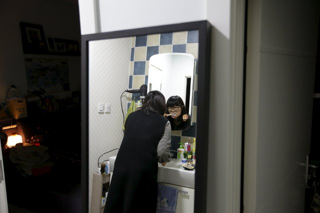 Li Nan, a makeup artist, brushes her teeth at home in Tianjin, before she leaves for Beijing, China, for work, November 18, 2015. Li wakes up at 5:30am to commute from Tianjin to Beijing, using a combination of bus, high-speed train and subway. (Photo by Jason Lee/Reuters)