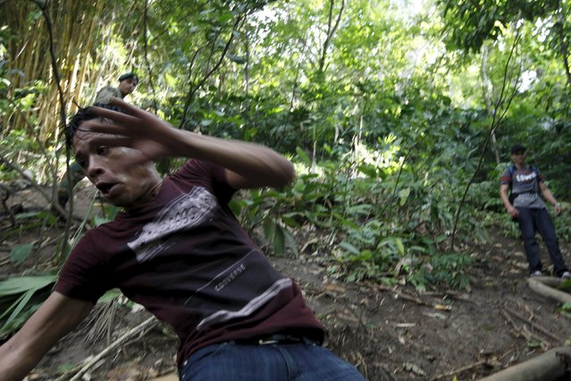A Cuban migrant slides down a hill after he crossed the border from Colombia through the jungle into La Miel, in the province of Guna Yala, Panama November 29, 2015. (Photo by Carlos Jasso/Reuters)