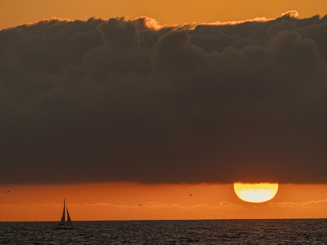 A sailboat glides on the Pacific Ocean off the coast of Venice Beach during sunset in Los Angeles, Sunday, December 27, 2020. Southern California's first significant storm of the season is expected to bring rain and snow to the region Sunday night through Monday, according to the National Weather Service. (Photo by Damian Dovarganes/AP Photo)
