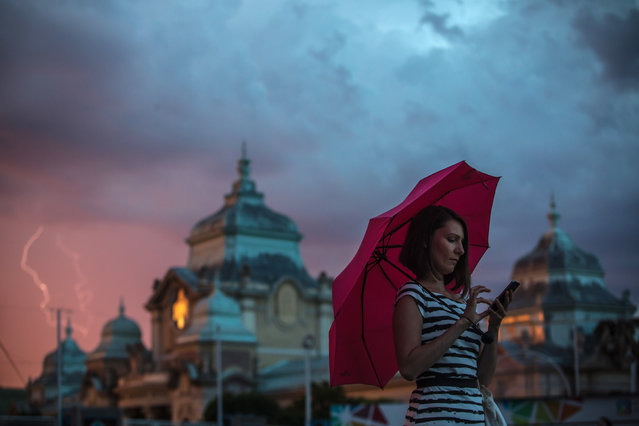 A woman holds an umbrella while using her mobile phone as a lightning storm rolls in, Prague, Czech Republic, 30 July 2017. Meteorologists predict summer temperatures of around 32 degrees Celsius in the Czech Republic over coming days. (Photo by Martin Divisek/EPA)