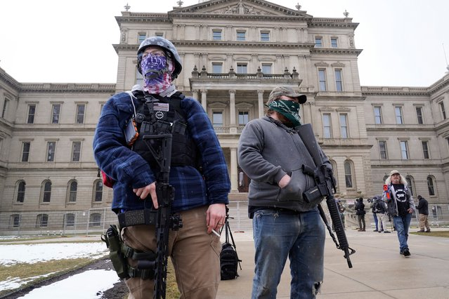 Two men with rifles stand outside the state Capitol in Lansing, Mich., Sunday, January 17, 2021. (Photo by Paul Sancya/AP Photo)