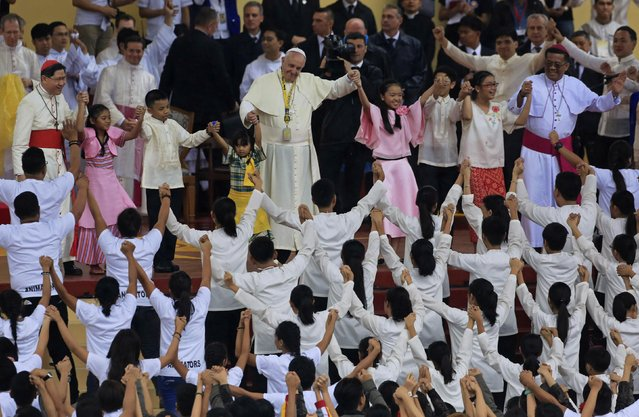 """Pope Francis joins hands with children while students perform during a meeting with youth at the University of Santo Tomas in Manila January 18, 2015. An emotional Francis, moved by the tears of an abandoned child, said on Sunday the world needed to """"learn how to cry"""" over the plight of the millions of poor, hungry, homeless and abused children. (Photo by Romeo Ranoco/Reuters)"""