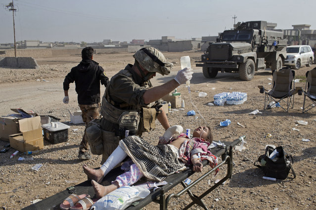 In this Sunday, November 6, 2016 photo, Derek Coleman, center, a volunteer medic, treats a wounded Iraqi special forces soldier at a field clinic in Gogjali, on the eastern outskirts of Mosul, Iraq. At the field hospital, teams of Iraqi and Western volunteer medics are treating a family badly burned by a car bomb, children maimed by booby-trapped explosives and soldiers suffering from shrapnel and gunshot wounds. (Photo by Marko Drobnjakovic/AP Photo)