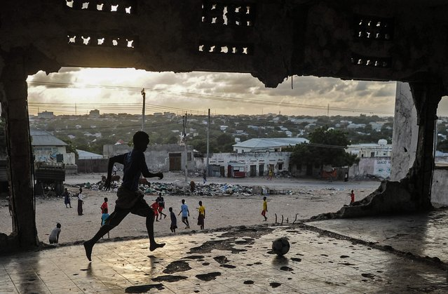 Somali children play football on a bulidling's upper floor as the sun sets in Mogadishu, Somalia, on June 7, 2018. (Photo by Mohamed Abdiwahab/AFP Photo)